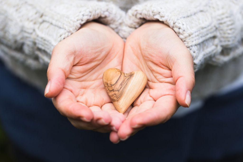Mãos juntas, em formato de conha, com uma pedra em formato de coração