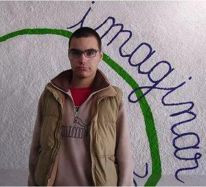 Jovem utente da APPACDM no centro socioeducativo junto à pintura imaginar