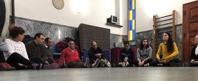 Utentes da APPACDM sentados num salão de ginástica em atividade com auxiliar