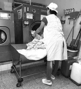 Utente da APPACDM a retirar a roupa da máquina de lavar